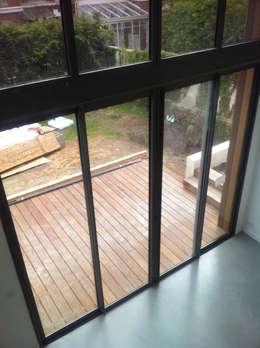 la double hauteur du séjour avec le béton ciré et la terrasse en teck: Salon de style de style Moderne par Eric Rechsteiner