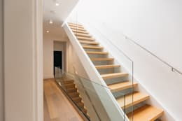 Beautiful wood stairs with glass panel railing:  Corridor & hallway by FLUID LIVING STUDIO