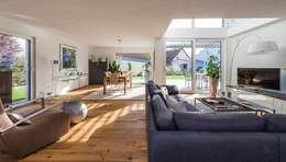 Wohnbereich mit darüber liegender Galerie und Zugang zur Terrasse: moderne Wohnzimmer von KitzlingerHaus GmbH & Co. KG