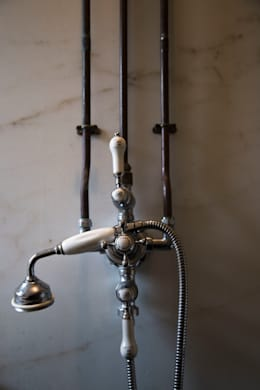 Shower mounted on recalimed Colorado Gold marble slab:   by Research + Design