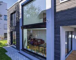 Panoramascheiben lassen viel Licht in die großzügig gestalteten Wohnräume: moderne Häuser von KitzlingerHaus GmbH & Co. KG