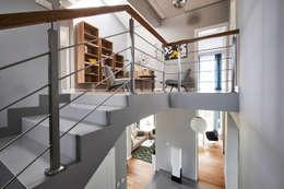Schody i biblioteka na górze: styl , w kategorii Korytarz, przedpokój zaprojektowany przez Mhomestudio