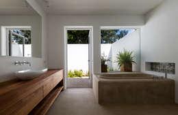 Bañera de hormigón y mueble de baño de madera con vistas al jardín.: Baños de estilo mediterráneo de Alejandro Giménez Architects