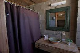 La Amistad Cottages: Banheiros rústicos por Studio Defferrari