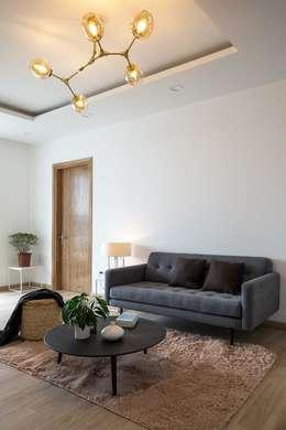 Thảm trải sàn cùng bộ sofa đơn giản nhưng mang lại cảm giác sang trọng.:  Phòng khách by Công ty TNHH Xây Dựng TM DV Song Phát
