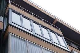 Cerramiento de balcón en PVC con acabado metálico: Casas adosadas de estilo  de Soluvent Window Solutions