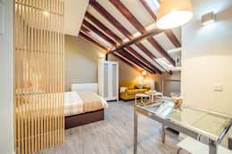 Reforma de vivienda abuhardillada en Madrid Centro.: Salones de estilo moderno de Arkin