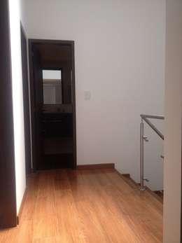 Pasillo con piso de laminado de madera, escalera y vista a cuartos: Pasillos y vestíbulos de estilo  por Erick Becerra Arquitecto