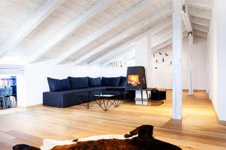 Dachausbau: rustikale Wohnzimmer von BESPOKE GmbH // Interior Design & Production