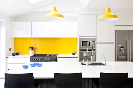 White, black, stainless steel and a vibrant splash of yellow.: modern Kitchen by Pyram