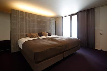 或る住宅地のヴィラ: MooS/ムースが手掛けた寝室です。