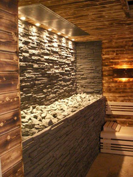 Gewerbliche Design-Sauna mit Natursteinwand hinter dem Saunaofen.:  Sauna von corso sauna manufaktur gmbh