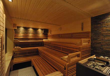 Professionelle Design-Sauna mit beleuchteter Natursteinwand.:  Sauna von corso sauna manufaktur gmbh