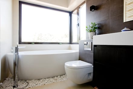 Baños de estilo rústico por IPUNTO INTERIORISMO