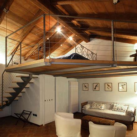 Camera con soppalco: Hotel in stile  di Architetti Barbero Associati