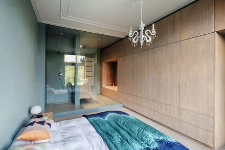 slaapkamer met ensuite badkamer, kledingkast loopt door in kast waar een bad in staat: moderne Slaapkamer door StrandNL architectuur en interieur