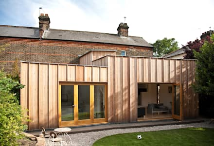 Rear elevation showing timber extension: modern Houses by Neil Dusheiko Architects