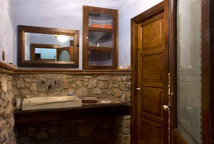 Restauración de masia guardando la esencia de los años: Baños de estilo rústico de Puigdesens fusteria interiorisme