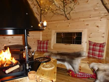 The interior of a 10m² cabin, fire going lovely cushions and reindeer skins on the benches. : scandinavian Garden by Arctic Cabins