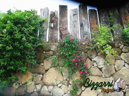 Detalhe do muro com os dormentes: Piscinas rústicas por Bizzarri Pedras
