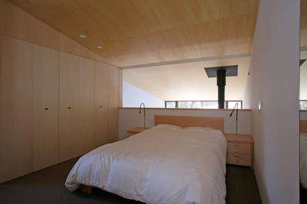 木立に佇む家: 設計事務所アーキプレイスが手掛けた寝室です。
