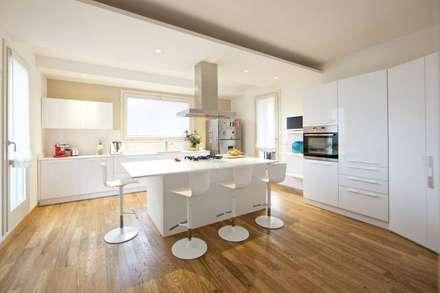 Cucina bianca con isola centrale e cappa in acciaio: Cucina in stile in stile Moderno di Modularis Progettazione e Arredo