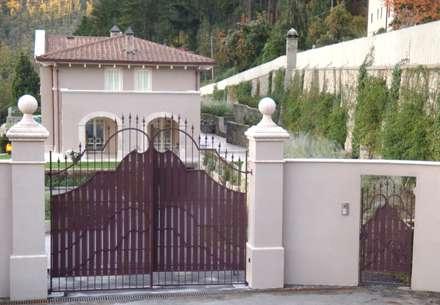 Ingresso della villa: cancello carrabile e cancello pedonale con elementi decorativi per le colonne: Garage/Rimessa in stile in stile Classico di Garden House Lazzerini
