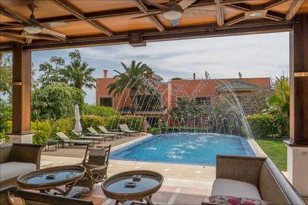 Vista a la piscina desde el pabellón: Piscinas de estilo tropical de Hansen Properties