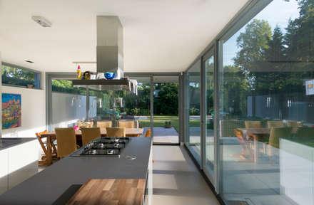 De woonkeuken met overdekt terras en volledig zicht op tuin: moderne Keuken door Architect2GO