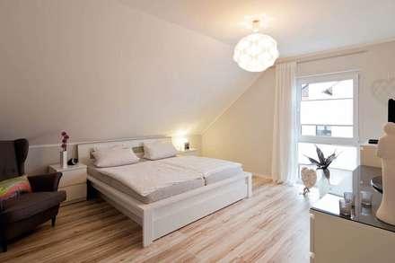 Schlafzimmer des VIO 302 - Wohnglück im Grünen: moderne Schlafzimmer von FingerHaus GmbH