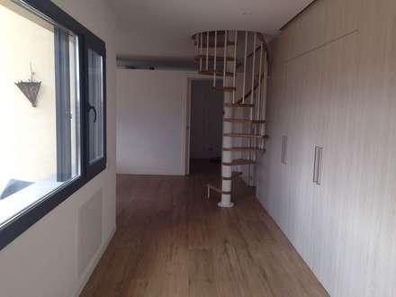 Vista del vestibulo desde la entrada, con la escalera de caracol para acceder al altillo, y  la pared equipada con armarios encastados para almacenamiento y las puertas para acceder a las habitaciones y a los baños: Pasillos y vestíbulos de estilo  de CRE3A Creative Design Solutions