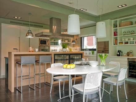 Dos áreas de comidas: el office y la barra para los desayunos informales: Cocinas de estilo moderno de DEULONDER arquitectura domestica