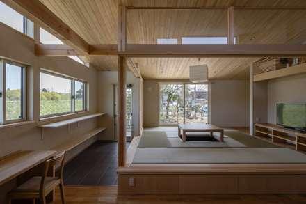 庭を楽しみながら暮らす家: アトリエグローカル一級建築士事務所が手掛けたリビングです。