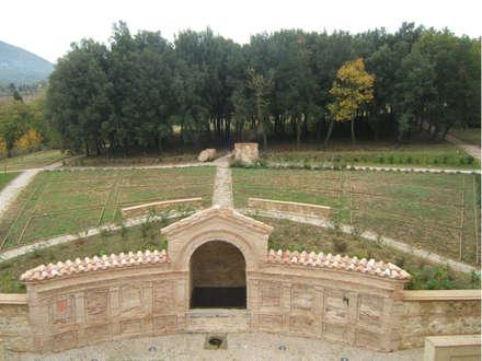 Vista verso il retro del giardino: la grande esedra con il boschetto di lecci.: Musei in stile  di Architetti Laura Romagnoli e Guido Batocchioni Associati