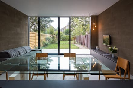 View over dining table with living area and garden beyond: industrial Dining room by Mustard Architects