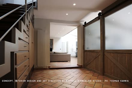 Entrance and the double slidign BARN doors designed by Rachele Biancalani: Spogliatoio in stile  di Rachele Biancalani Studio - Architecture & Design