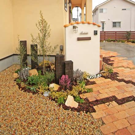 アンティーク調レンガのアプローチの南欧風エクステリア: 有限会社 匠ガーデンが手掛けた庭です。