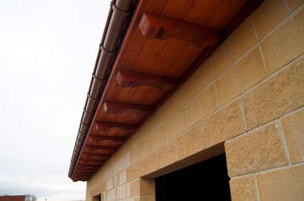 Alero con panel sandwich de madera con núcleo aislante y acabado decorativo en friso abeto barnizado panelestudio.: Paredes de estilo  de panelestudio