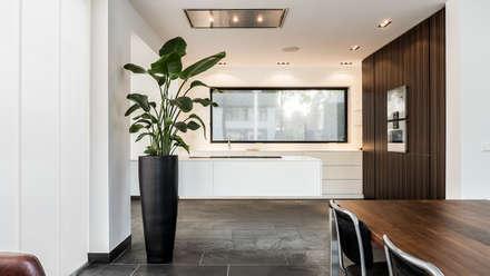 Luxe renovatie met zwevende dakopbouw, maatwerk keuken met zwevend HI-MACS keukenblok en houtfineer kastenwand: moderne Keuken door Joep van Os Architectenbureau