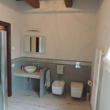 Bagno piano terra con pavimento in ceramica effetto legno e rivestimento a media altezza in mosaico con greca: Bagno in stile in stile Rustico di Nadia Moretti