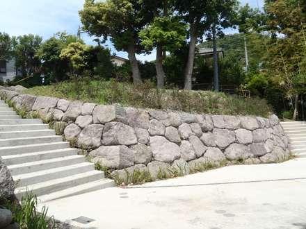 天然の真鶴石を使った石積み: 安達造園株式会社が手掛けた庭です。