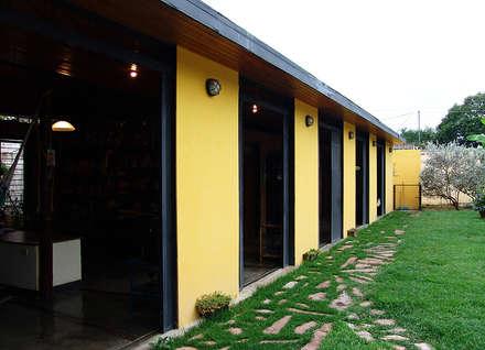Fachada este – Puertas corredizas abiertas: Casas de estilo  por YUSO