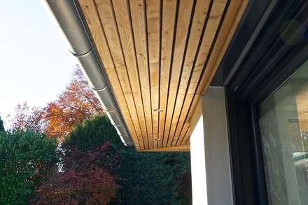 Dachunterschlag in Massivholz: moderne Häuser von GRID architektur + design