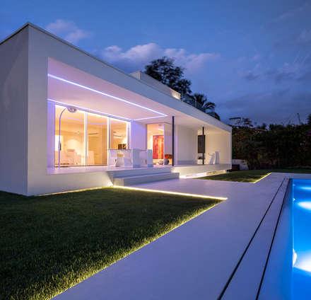 Herrero House - Exterior porch and pool at night: Casas de estilo mediterráneo de 08023 Architects