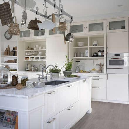 El entorno sobrio y relajantegana en sensación de amplitud gracias al mobiliario en blanco: Cocinas de estilo rústico de DEULONDER arquitectura domestica