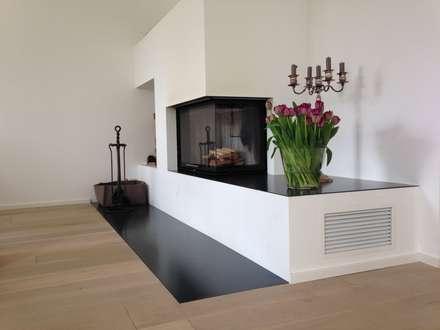 Moderner Eckkamin mit verlängertem Feuertisch: moderne Wohnzimmer von Christoph Lüpken Ofenbau GmbH