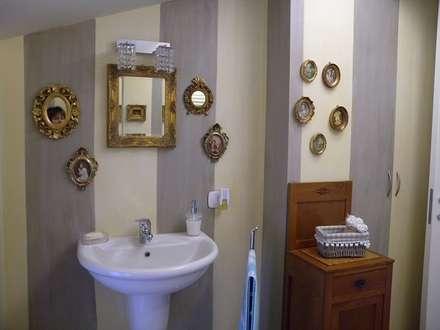 bagno a righe con quadri: Bagno in stile in stile classico di A2architetti