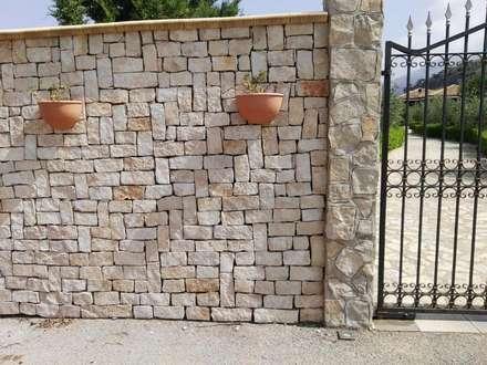 Rivestimento muro di recinzione con listelli tranciati in Pietra di Trani: Pareti in stile  di Cava di Trani