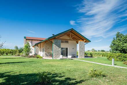 Una villa immersa nel verde: Casa di legno in stile  di Woodbau Srl