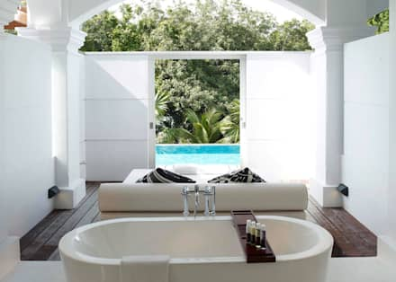 Outdoor bath and daybed:  Hotels by Deirdre Renniers Interior Design